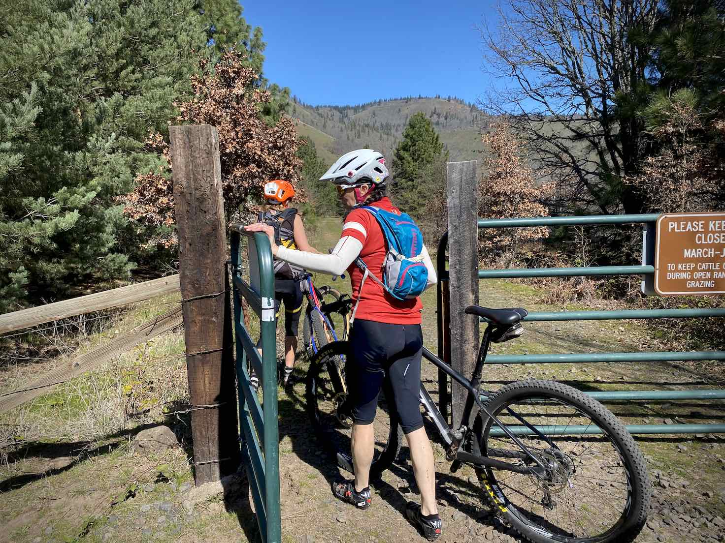 Cyclists passing through one of the several gates along the Klickitat Trail.