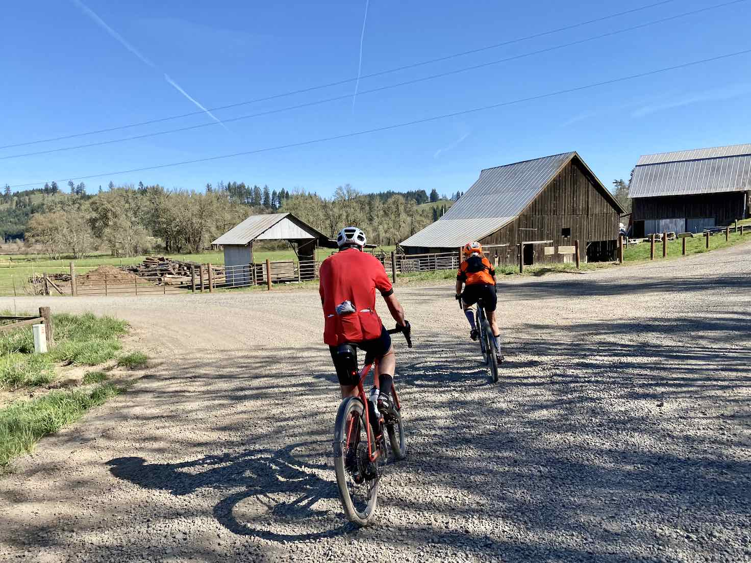 Two cyclists turning left on gravel road with old wooden barn in the distance.