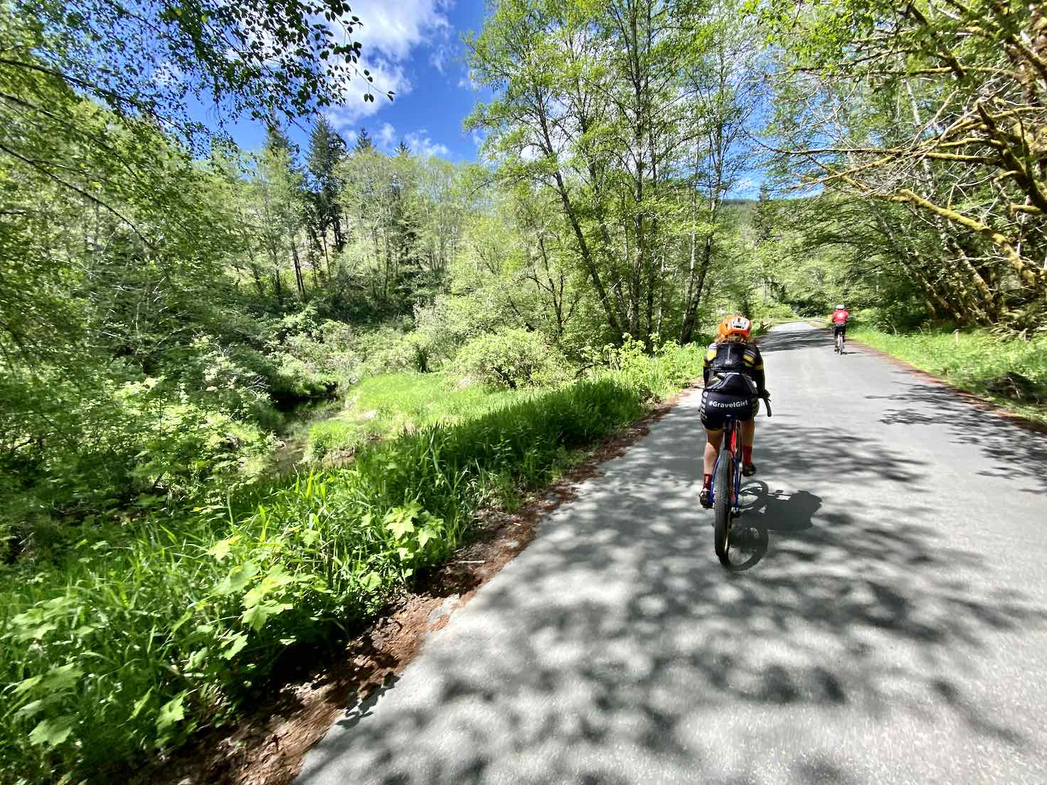 Woman cyclist on a bit of pavement near Drift Creek.