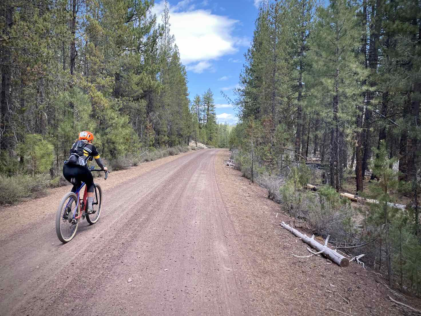 Woman gravel cyclist on red cinder road NF-43.
