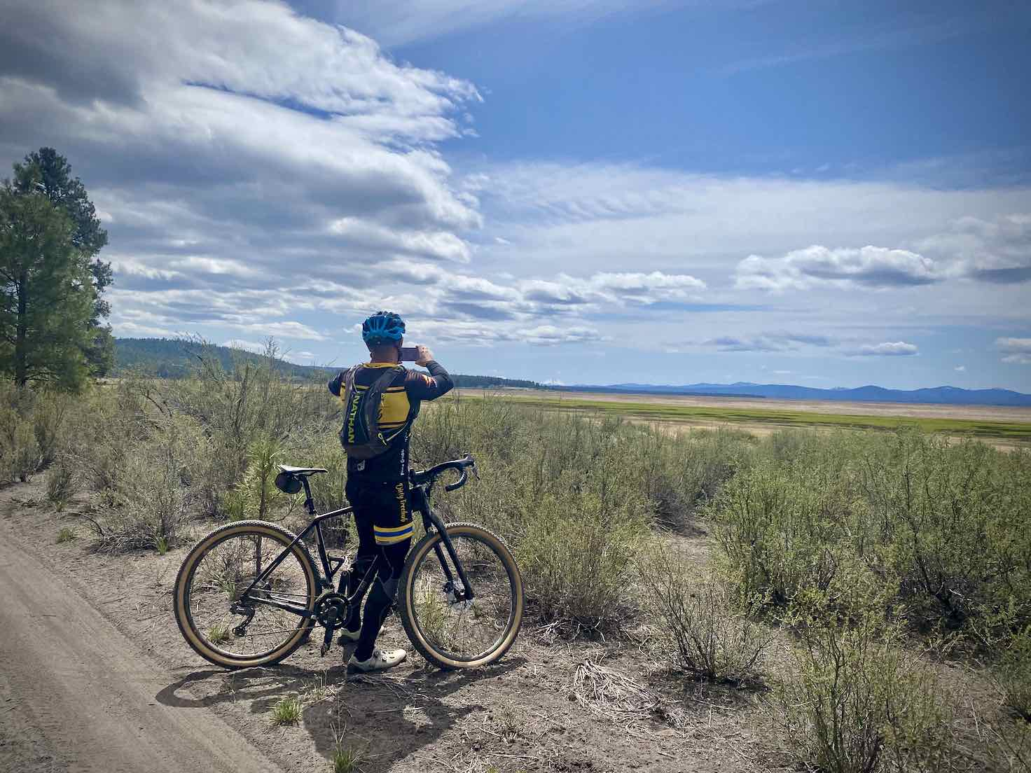 Cyclist taking a picture of the Klamath Marsh and Mount Scott.