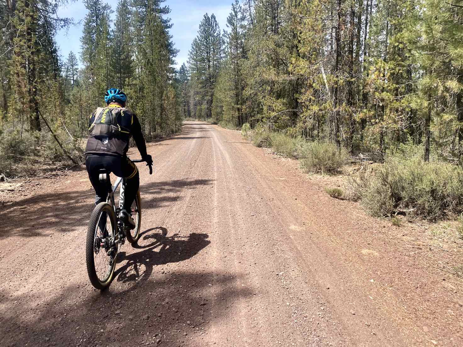 Gravel cyclist riding the red cinder road NF-43.