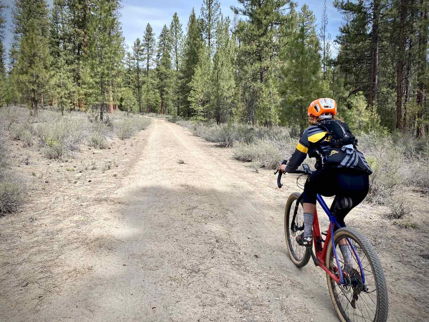 Woman gravel cyclist on white sand road near Wocus Butte.