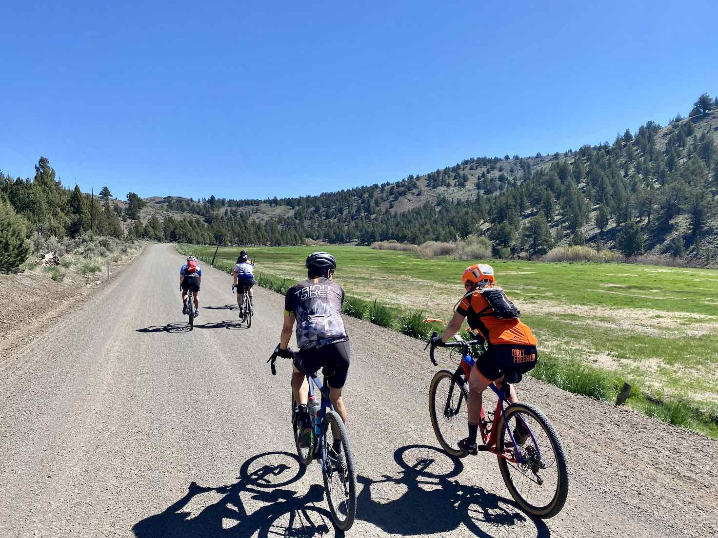 A group of cyclist riding gravel near Brothers, OR with Bear Creek off in the distance.