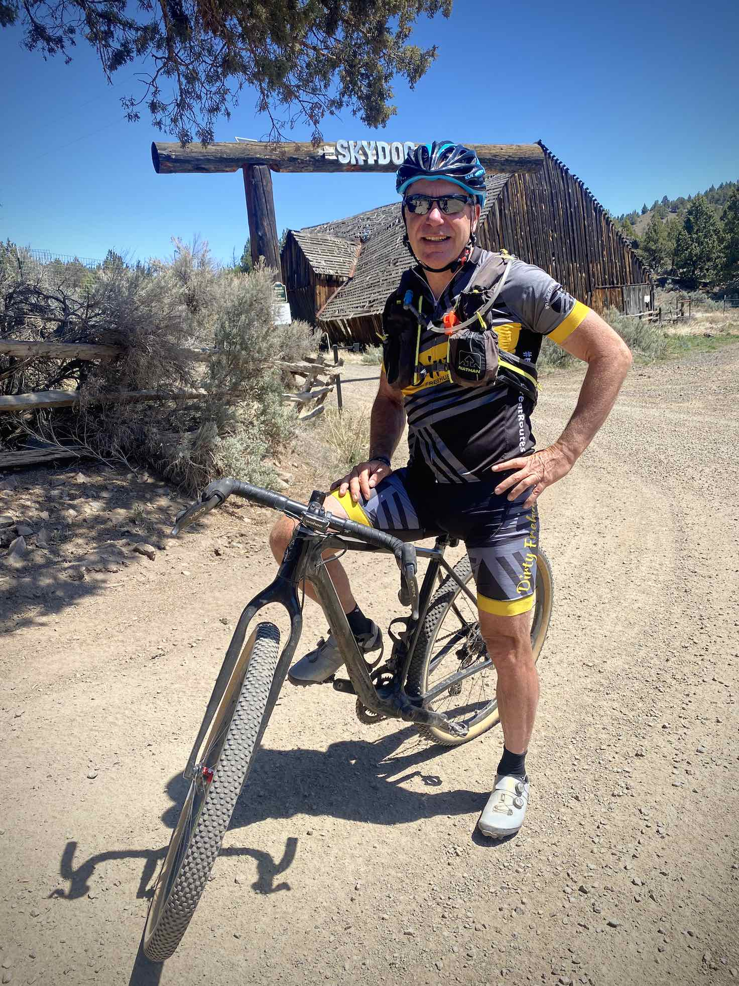 Gravel cyclist in front of the Skydog Ranch sign.