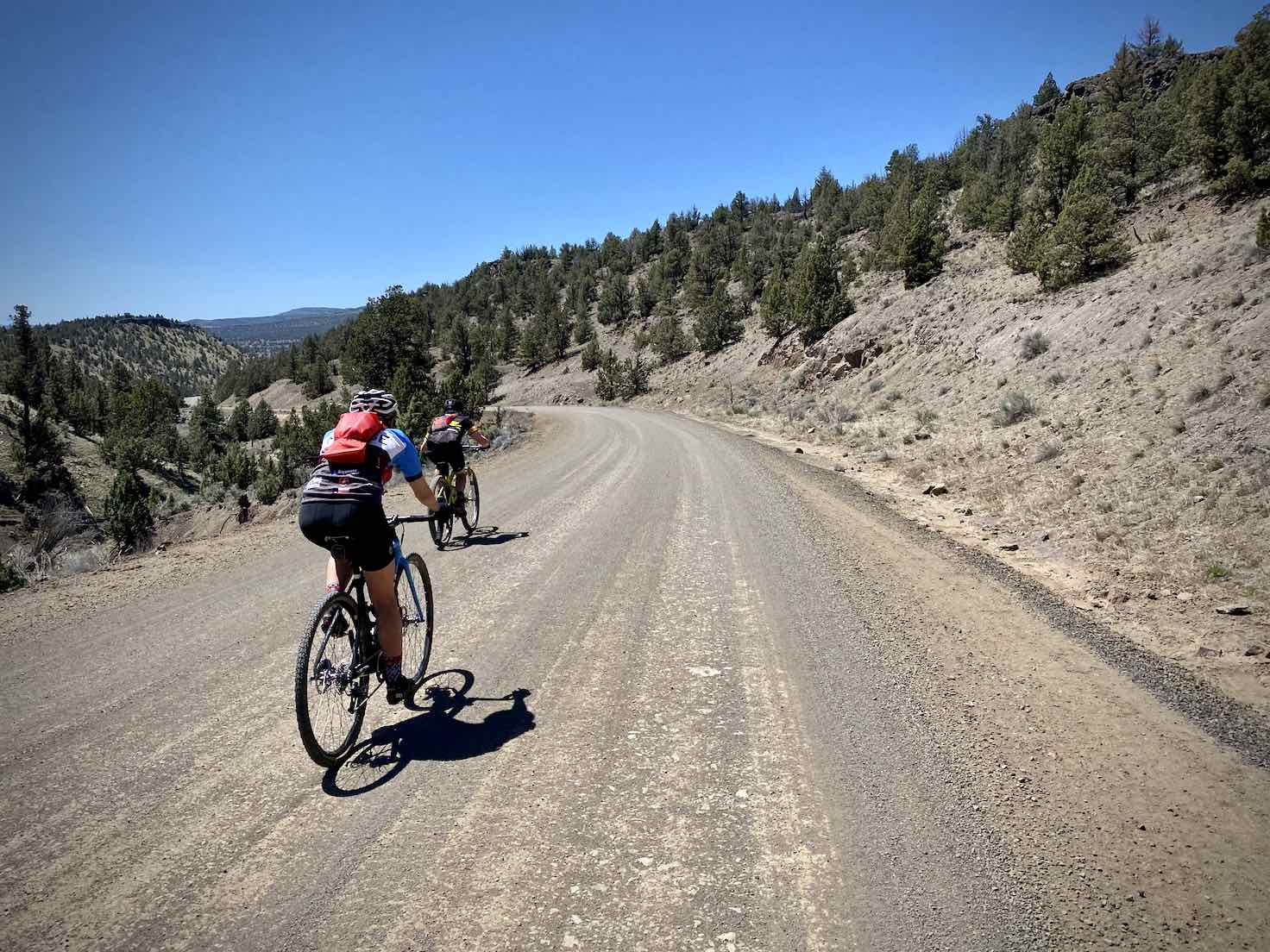 Two cyclists descending fast on Salt Creek Road near the Prineville Reservoir.