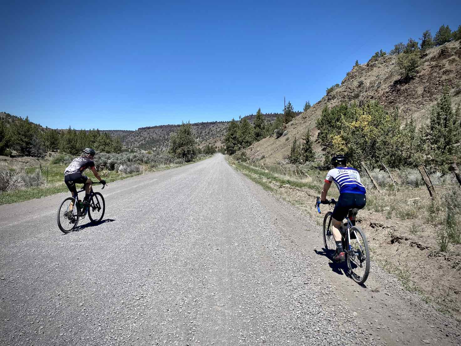 Two cyclists riding the gravel portion of the Crooked River Highway.
