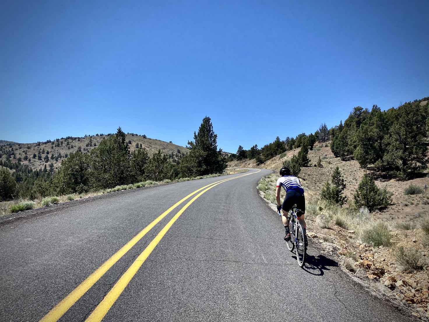 Cyclist climbing an uphill pitch on the Crooked River Highway.