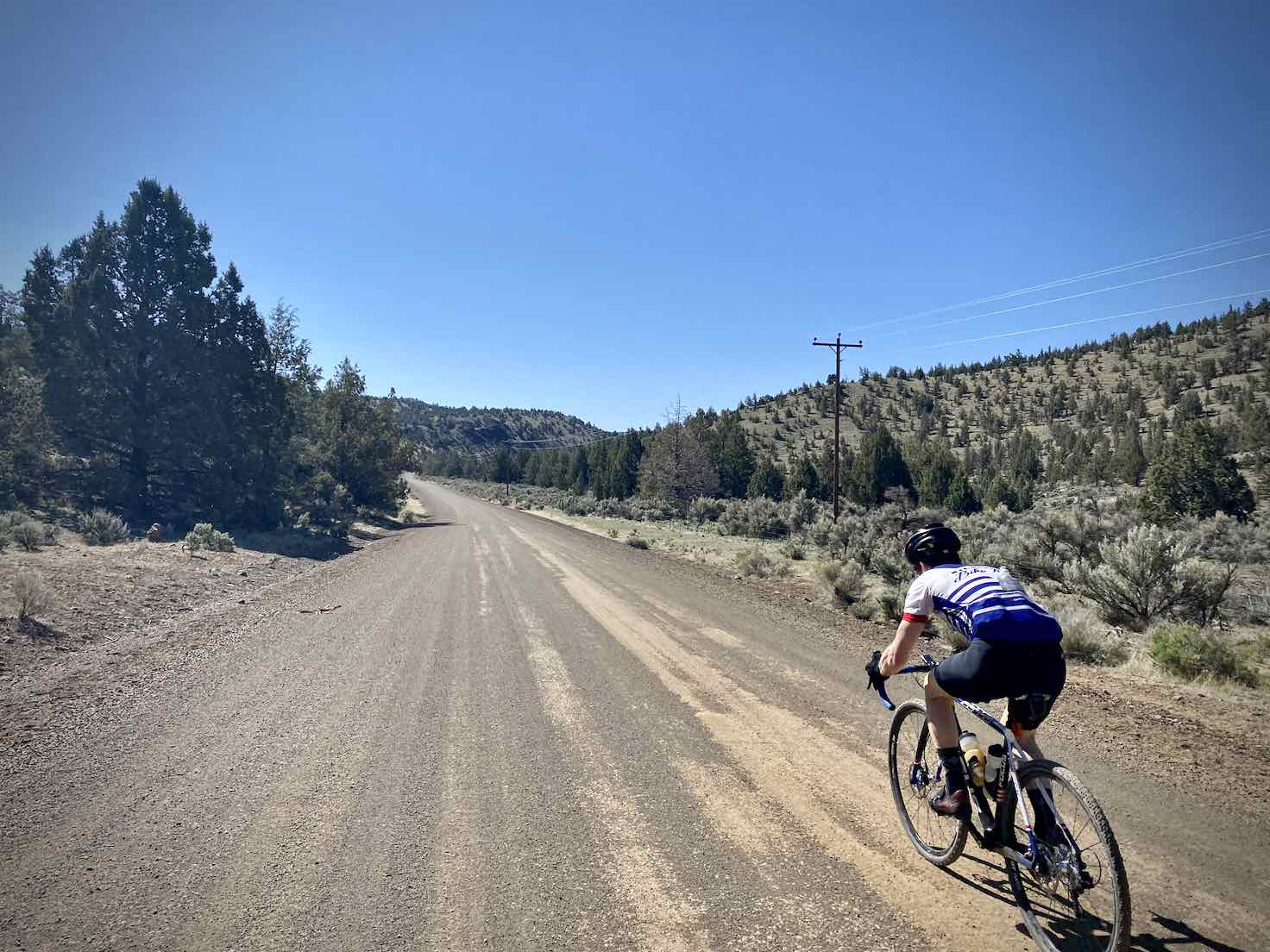 Cyclist going fast on the gravel portion of Bear Creek Road.