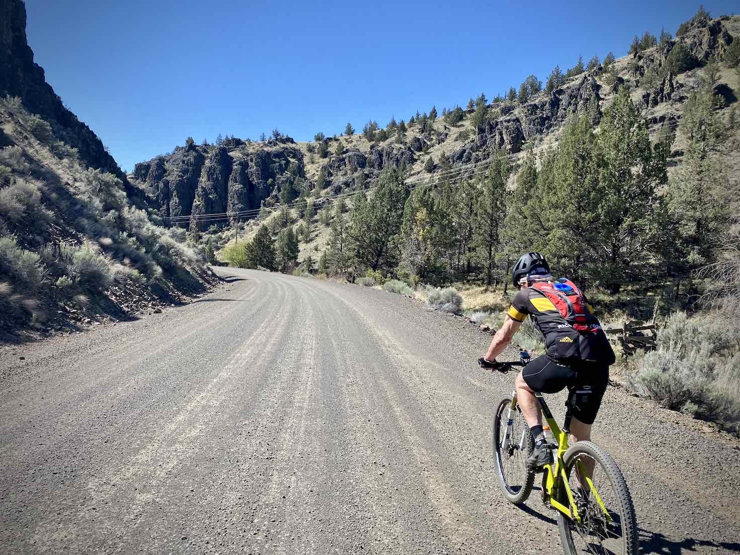 Biker on mountain bike on gravel road near Prineville, OR.