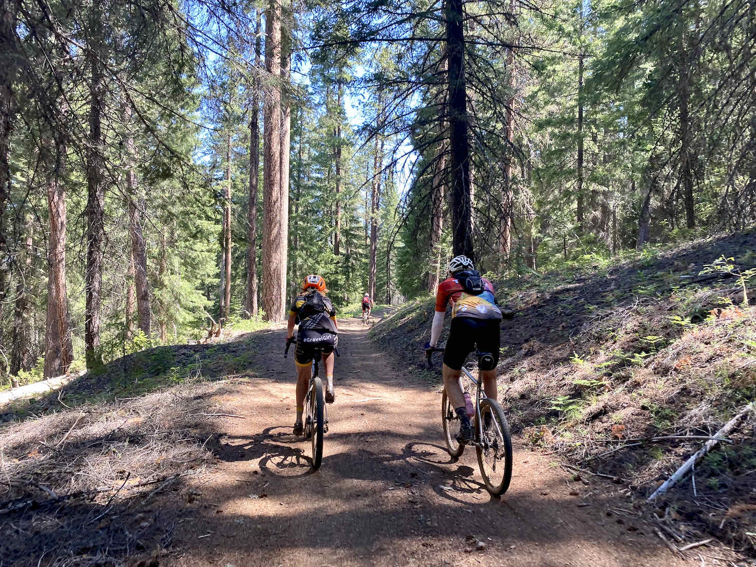 A couple of gravel cyclists riding shoulder to shoulder on the Black Butte dirt roads.