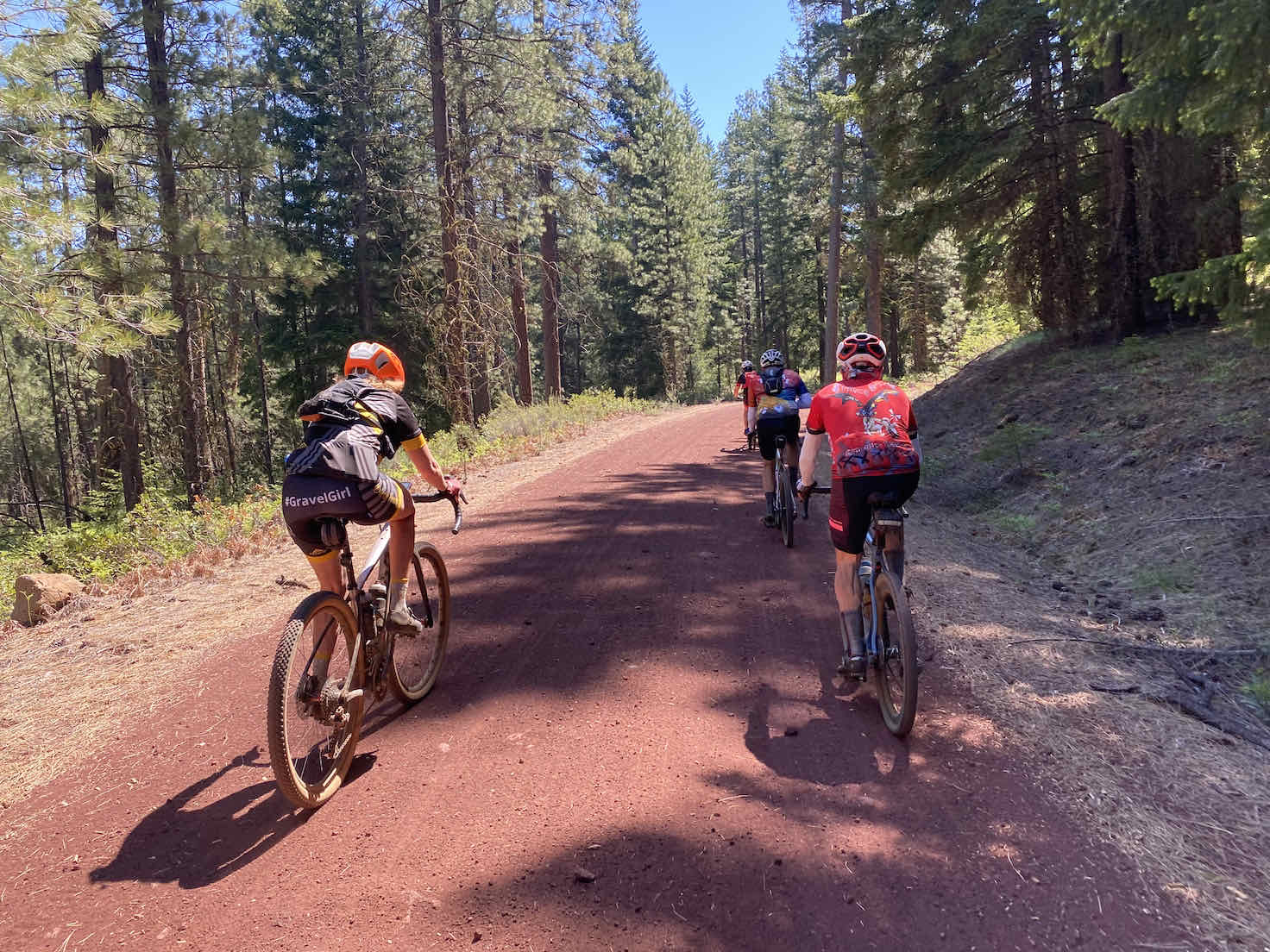 A group of gravel cyclists climbing up the red cinder road on the north side of Black Butte.